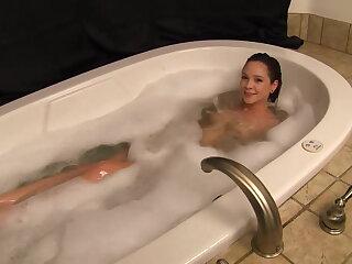 Young hottie getting massaged in a bathtub